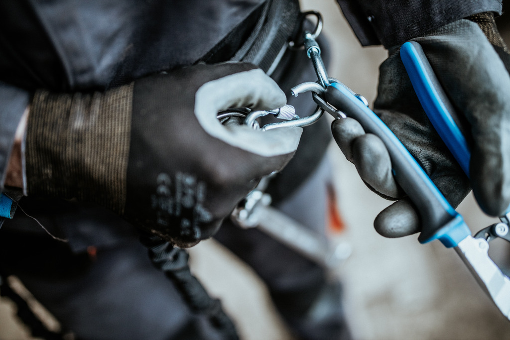 The carabiner on the lanyard is attached to the ring on the tool. The rings on the tools are large enough to accept 2 carabiners.