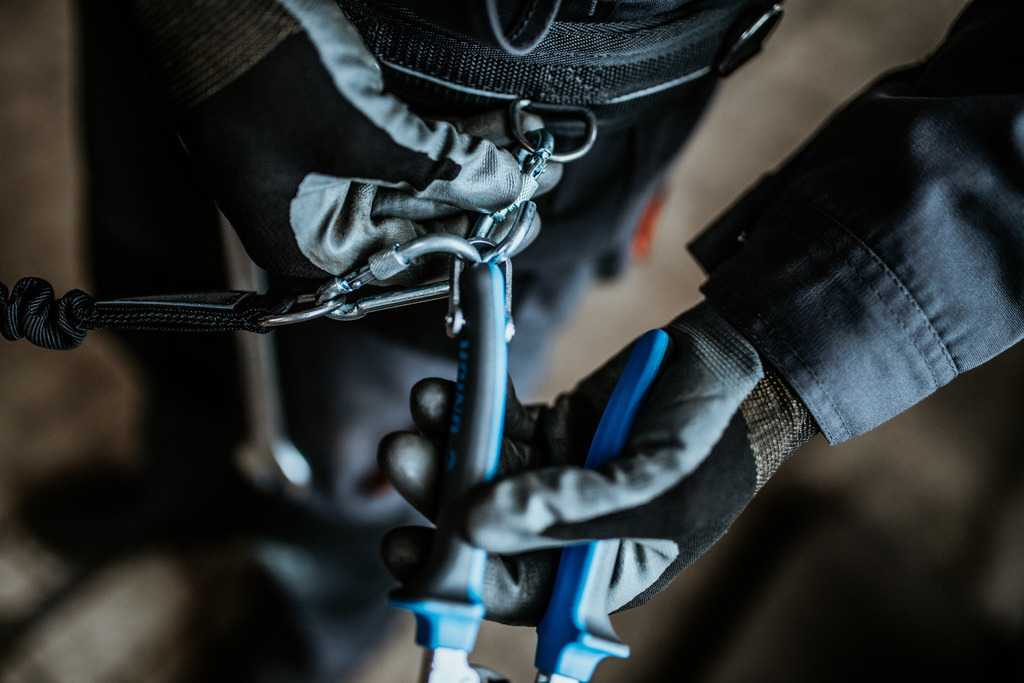 Open the carabiner on the belt and remove the tool, which is attached to a lanyard, from the carabiner on the belt. The tool is now ready for use.